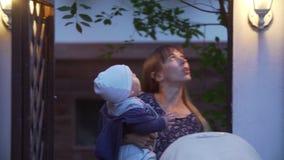 A mãe com o filho vai nivelando a caminhada A mãe com a criança vai para uma caminhada na rua da noite Mostras da mãe ao video estoque