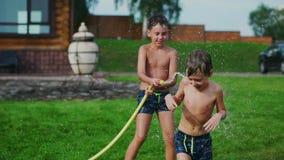 Mãe com o pai e as duas crianças que jogam na água de derramamento do gramado que ri e que tem o divertimento no campo de jogos c filme