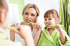 Mãe com os dentes da escova da criança fotografia de stock
