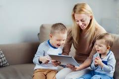 Mãe com os dois filhos que jogam a tabuleta digital Fotografia de Stock Royalty Free