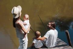 A mãe com pouca filha em suas mãos está olhando como pesca do pai e do filho Toda a família vestida na roupa branca fotos de stock royalty free
