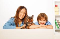 A mãe com seu filho e o cão de Yorkshire colocam no sofá Fotos de Stock