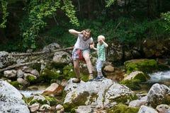 Mãe com seu filho que faz as caras engraçadas, tendo o divertimento por um córrego da montanha em uma viagem da família imagens de stock