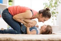 A mãe com sua criança está tendo o rolamento do divertimento em um assoalho imagens de stock royalty free