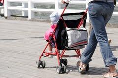 Mãe com sua criança no passeio do carrinho de criança foto de stock