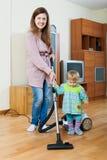 Mãe com sua criança que faz a limpeza home imagem de stock royalty free