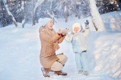 Mãe com sua criança que joga no inverno Imagem de Stock