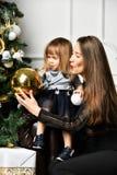 Mãe com sua filha da criança que comemora perto da árvore de Natal fotos de stock royalty free