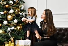 Mãe com sua filha da criança que comemora perto da árvore de Natal imagens de stock royalty free