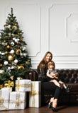 Mãe com sua filha da criança que comemora perto da árvore de Natal foto de stock royalty free