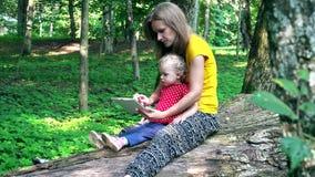 A mãe com sua filha da criança que usa o tablet pc senta-se no tronco de árvore caído video estoque