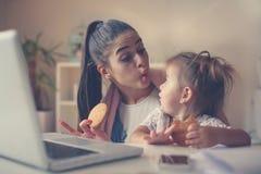 Mãe com sua filha em casa que tem o café da manhã e o valor máximo de concentração no trabalho foto de stock