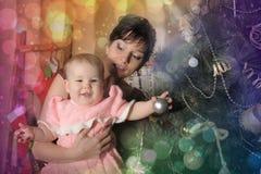 Mãe com sua filha em seus braços perto da árvore de Natal Fotografia de Stock