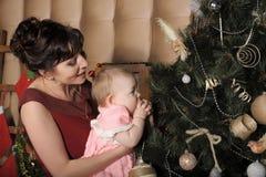Mãe com sua filha em seus braços perto da árvore de Natal Imagem de Stock Royalty Free