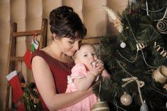 Mãe com sua filha em seus braços perto da árvore de Natal Foto de Stock Royalty Free