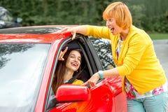 Mãe com sua filha perto do carro vermelho fotos de stock royalty free