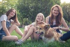 A mãe com suas filhas e o cão estão sentando-se em uma grama imagem de stock royalty free