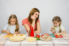 A mãe com ternura olha como sua filha pequena para ajudá-la na cozinha a preparar refeições Fotografia de Stock