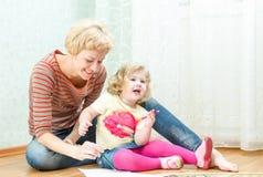 Mãe com um desenho pequeno da filha Fotografia de Stock