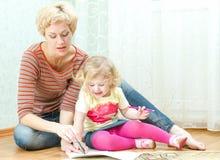 Mãe com um desenho pequeno da filha Fotos de Stock Royalty Free