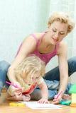 Mãe com um desenho pequeno da filha Fotos de Stock