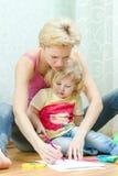 Mãe com um desenho pequeno da filha Foto de Stock Royalty Free