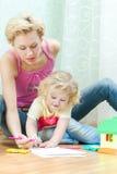 Mãe com um desenho pequeno da filha Imagem de Stock Royalty Free