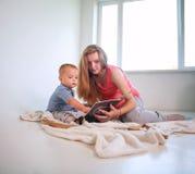 Mãe com um filho pequeno do bebê em um livro de leitura da sala em casa fotos de stock royalty free