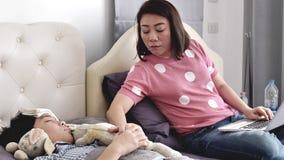 A mãe com uma criança tenta trabalhar em casa no laptop, um menino doente estava encontrando-se na cama video estoque