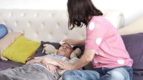 A mãe com uma criança tenta trabalhar em casa no laptop, um menino doente estava encontrando-se na cama vídeos de arquivo