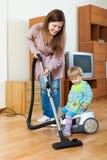 Mãe com uma limpeza do bebê na casa Foto de Stock Royalty Free