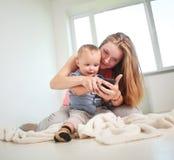 Mãe com uso do filho da criança pequena falar em casa no smartphone fotos de stock