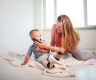 Mãe com uso do filho da criança pequena falar em casa no smartphone foto de stock royalty free