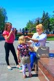 A mãe corrige seu cabelo do ` s da filha durante uma caminhada através da cidade da mola Foto de Stock