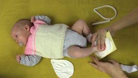 A mãe cria a pegada recém-nascida do bebê no material especial filme
