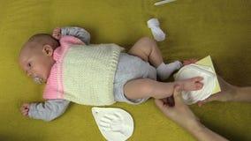 A mãe cria a pegada recém-nascida do bebê no material especial video estoque