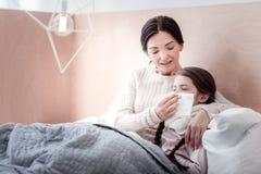 Mãe cuidadosa que encontra-se na cama com sua criança doente foto de stock royalty free