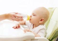 A mãe dá a água do bebê da garrafa plástica na casa da tabela Fotos de Stock