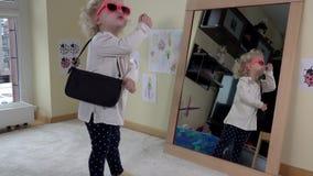 A mãe dá a bolsa e os óculos de sol para sua menina da filha que está o espelho próximo filme