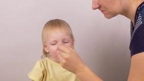 A mãe dá a sua filha caucasiano pequena da menina uma medicina em uma colher, a medicina para alergias e a constipação comum, bra video estoque