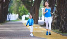 A mãe da família dos esportes e a filha da criança são contratadas em correr a imagens de stock