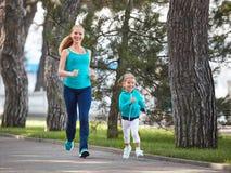 A mãe da família dos esportes e a filha da criança são contratadas em correr a fotografia de stock royalty free