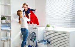 Mãe da família e ajudante pequeno do super-herói da menina da criança na lavanderia Imagem de Stock Royalty Free