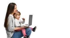 Mãe da família e filha da criança em casa com um portátil fotos de stock royalty free