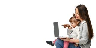 Mãe da família e filha da criança em casa com um portátil imagens de stock royalty free