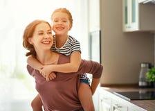 Mãe da família e filha da criança que abraça na cozinha foto de stock