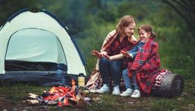 A mãe da família e a filha da criança aquecem suas mãos pela fogueira sobre imagens de stock royalty free