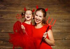 A mãe da família e a filha da criança comemoram Dia das Bruxas no diabo co Imagens de Stock