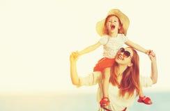Mãe da família e filha felizes da criança na praia no por do sol Fotografia de Stock