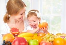 A mãe da família e a menina felizes da filha, comem o alimento saudável do vegetariano, fruto Imagens de Stock